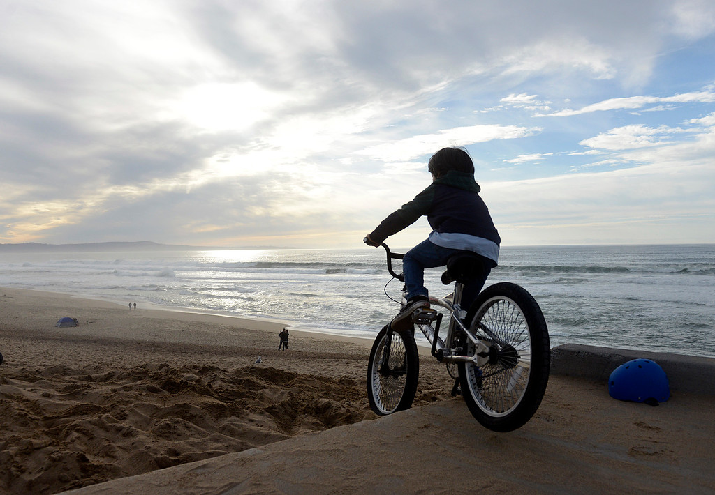. Mason Rola, 7, jumps his bike off the sidewalk and onto Marina Beach as cloud cover moves in on Friday afternoon November 25, 2016. (David Royal - Monterey Herald)