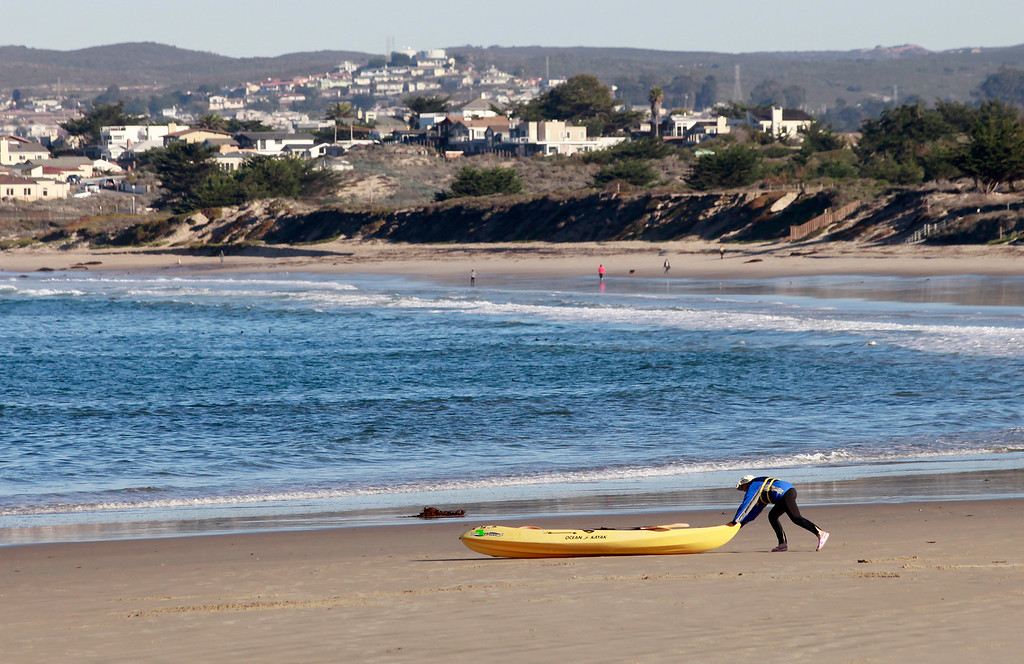 . A man pushes a kayak to the water on Del Monte State Beach in Monterey on a sunny Fall day on Tuesday, Nov. 29, 2016.  (Vern Fisher - Monterey Herald)