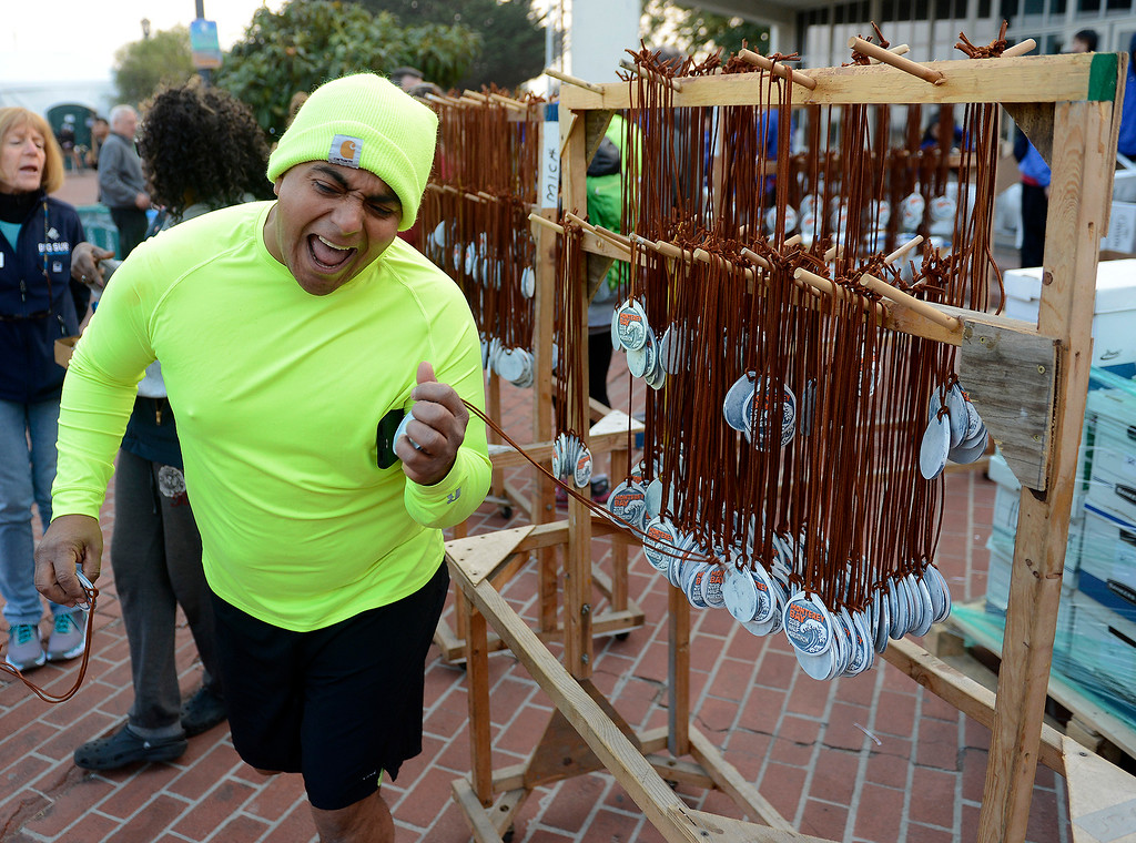 . David Aguirre from San Jose rejoices after receiving his medal from the Big Sur Half Marathon in Monterey on Sunday, November 11, 2018.  The Big Sur Half Marathon was cancelled due to poor air conditions from fire in northern California.  (Vern Fisher - Monterey Herald)