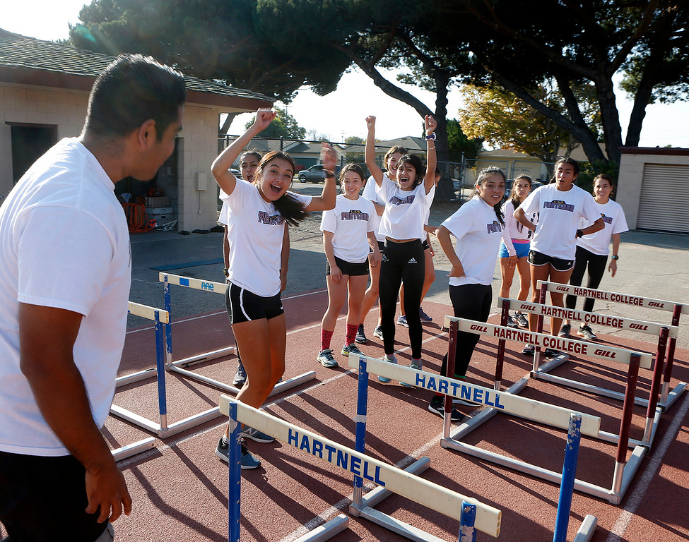 . Members of Hartnell College Women\'s Cross Country Team react after their coach Chris Zepeda, left, announced unexpectedly that he would be joining them on their run during practice at the Hartnell Track in Salinas on Wednesday November 14, 2018. (David Royal/ Herald Correspondent)