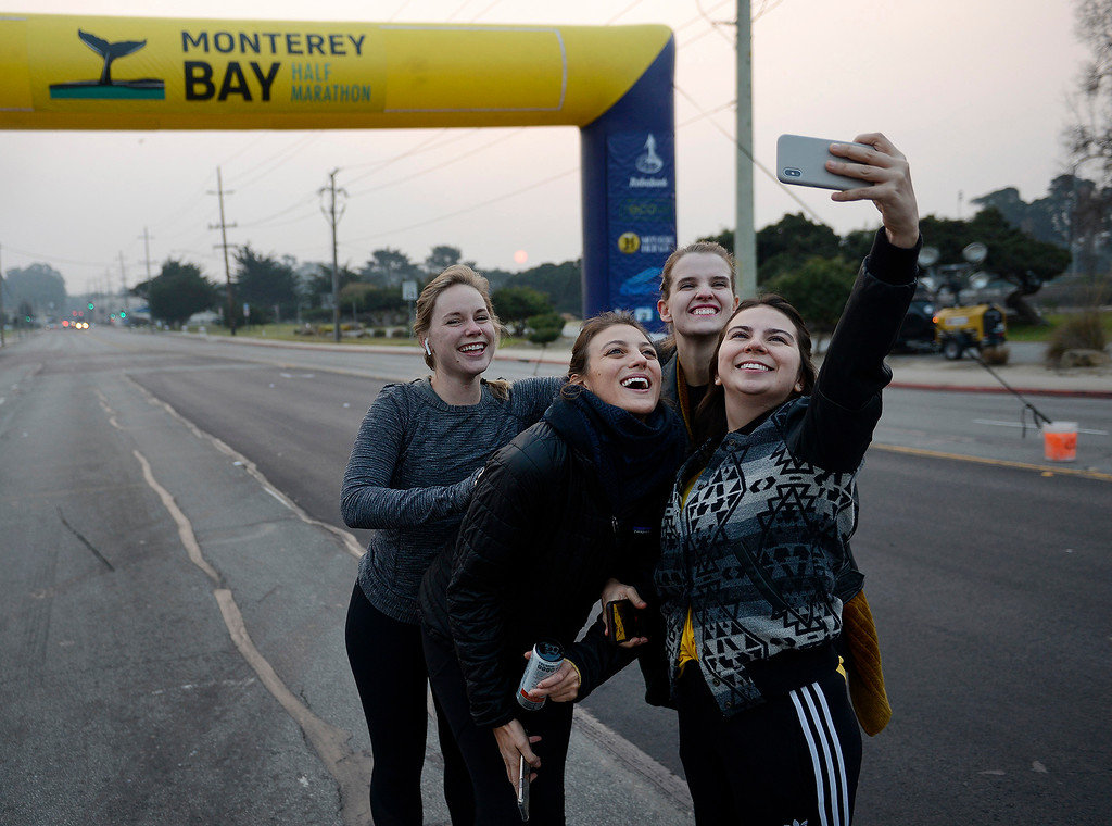 . A group of runners from Los Angeles take their photo at the start line of the Big Sur Half Marathon in Monterey on Sunday, November 11, 2018.  The Big Sur Half Marathon was cancelled due to poor air conditions from the Camp Fire in northern California.  (Vern Fisher - Monterey Herald)