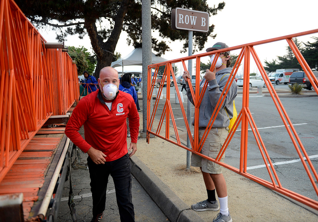. Race volunteer Russell Shugars wears a mask while removing barricades in Monterey on Sunday, November 11, 2018.  The Big Sur Half Marathon was cancelled due to poor air conditions from the Camp Fire in northern California.  (Vern Fisher - Monterey Herald)