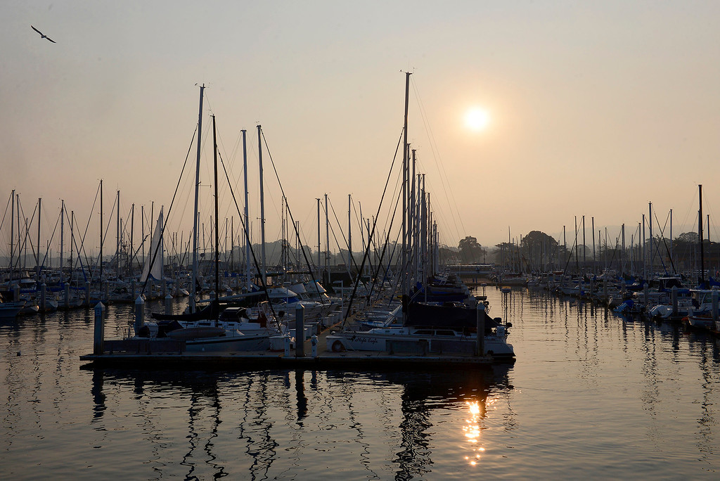 . The sun rises through heavy smoke over the Monterey Harbor in Monterey on Sunday, November 11, 2018.  The Big Sur Half Marathon was cancelled due to poor air conditions from the Camp Fire in northern California.  (Vern Fisher - Monterey Herald)