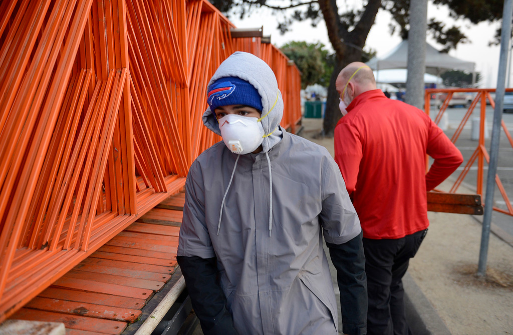 . Race volunteers wear masks while removing barricades in Monterey on Sunday, November 11, 2018.  The Big Sur Half Marathon was cancelled due to poor air conditions from the Camp Fire in northern California.  (Vern Fisher - Monterey Herald)