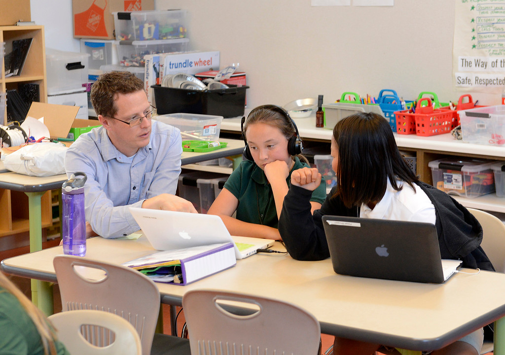 . Shane Whitman works with students Maile Maddox and Paige Shugart in class at Chartwell School in Seaside on Thursday, November 15, 2018.  (Vern Fisher - Monterey Herald)