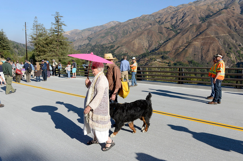 . Big Sur residents Clovis Harrod and Grady Cook walk on the new Pfeiffer Canyon Bridge with their dog Sander during the opening celebration on Friday, Oct. 13, 2017 after eight months of construction and $24 million.   (Vern Fisher - Monterey Herald)