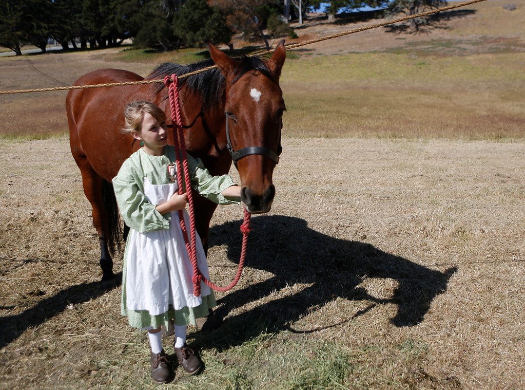 . Emelia Campbell, 9, pets a horse while dressed in Civil War period clothing at the encampment at the Lower Presidio Park in Monterey on Saturday October 14, 2017. The event was part of History Fest. (David Royal/Herald Correspondent)