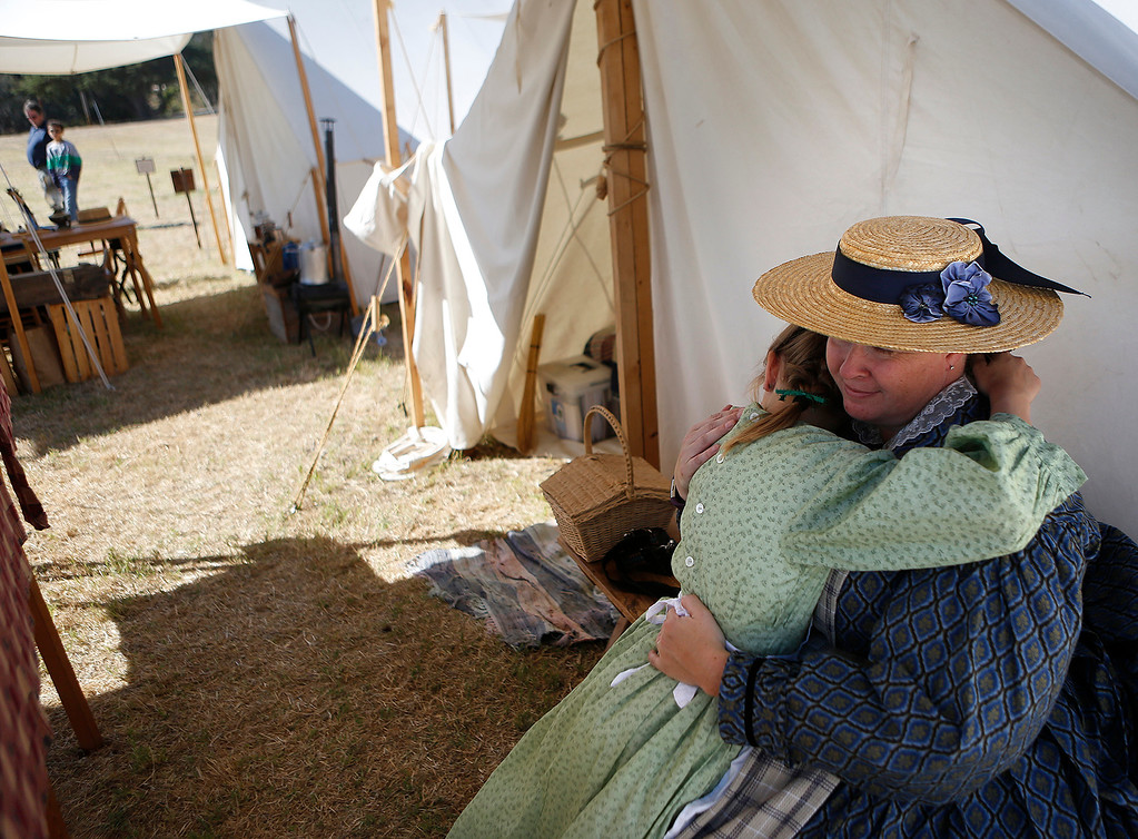 . Rachelle Campbell embraces her daughter Emelia, 9, who were dressed in Civil War period clothing at the encampment at the Lower Presidio Park in Monterey on Saturday October 14, 2017. The event was part of History Fest. (David Royal/Herald Correspondent)