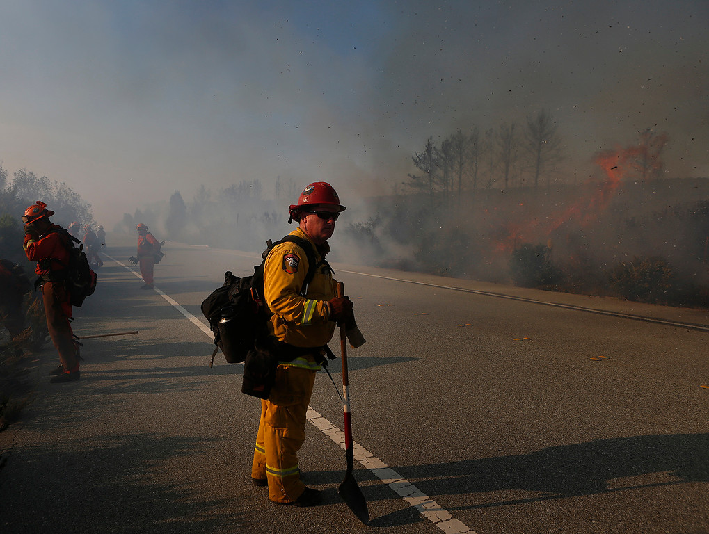. A firefighter and inmate crew keep guard for flare ups as sparks from a wildland fire fill the air along South Boundary Road in Fort Ord near Ryan Ranch in Monterey on Sunday October 15, 2017. (David Royal/Herald Correspondent)