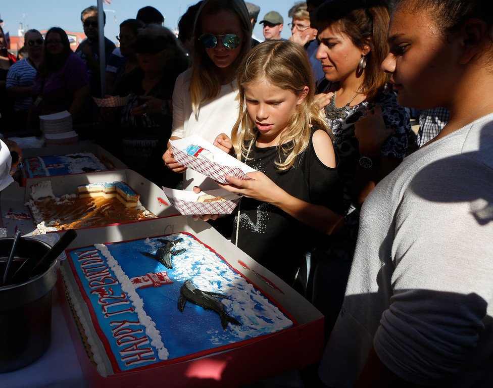 . Sara Hair of Denmark carries off birthday cake that was given out as Fisherman\'s Wharf celebrates its 172 birthday in Monterey on Sunday October 15, 2017. (David Royal/Herald Correspondent)
