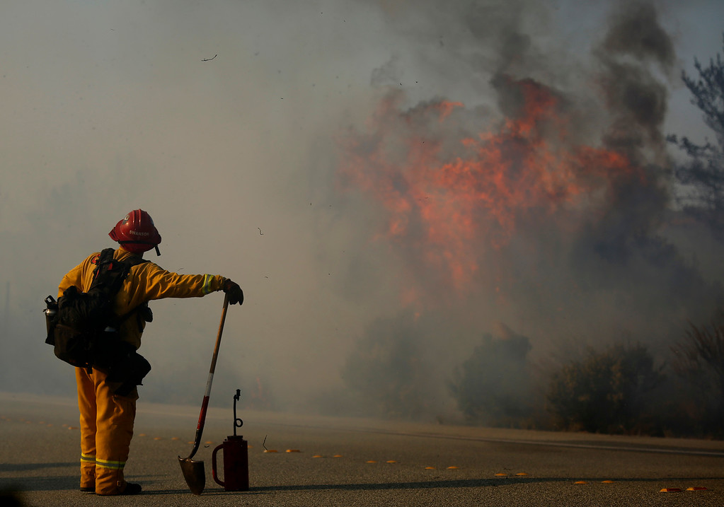 . A firefighter keeps eyes on a flaring wildland fire along South Boundary Road in Fort Ord near Ryan Ranch in Monterey on Sunday October 15, 2017. (David Royal/Herald Correspondent)