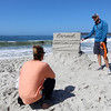 Todd Weaver, right, of Carmel explains how his entry titled Carmel Postcard is designed to line up exactly with the trees in the background, the horizon, and the waves crashing onto the beach and the best angle to view it during the Great Sand Castle Contest of Carmel on Sunday, October 4, 2015 in Carmel by the Sea, Calif. (Vernon McKnight/Herald Correspondent)