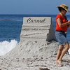 A woman walks past contestant Todd Weaver's entry titled Carmel Postcard after taking a photo during the Great Sand Castle Contest of Carmel on Sunday, October 4, 2015 in Carmel by the Sea, Calif. (Vernon McKnight/Herald Correspondent)