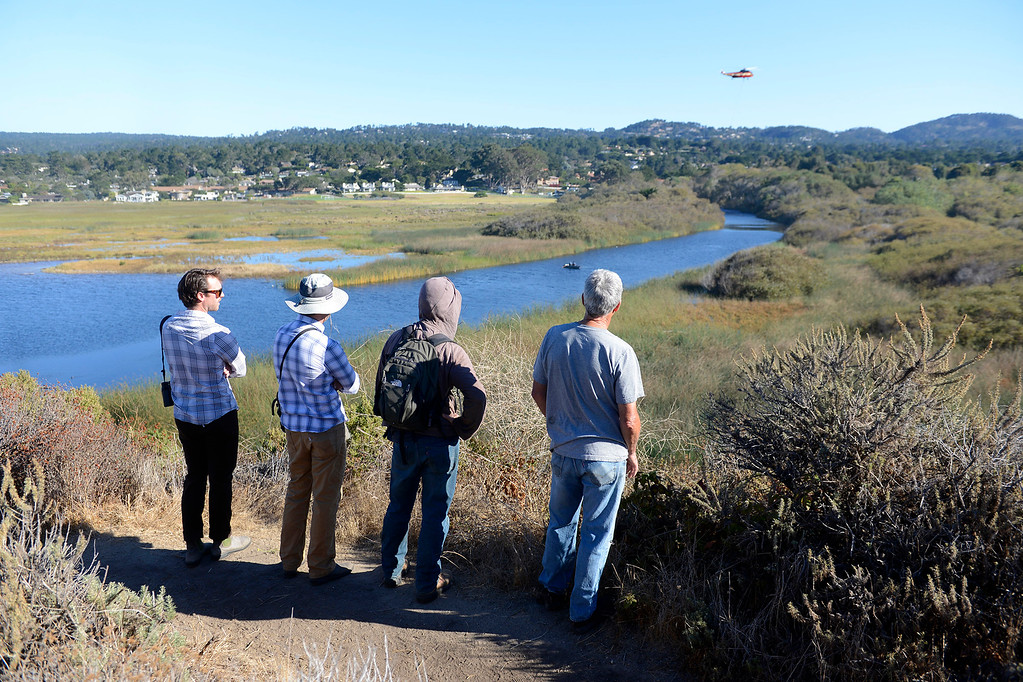 . People gather to watch as a helicopter was used to place large boulders, root balls and logs in the Carmel River estuary on Wednesday, Oct. 25, 2017 in an effort to improve fish habitat for the federally protected steelhead trout.  (Vern Fisher - Monterey Herald)