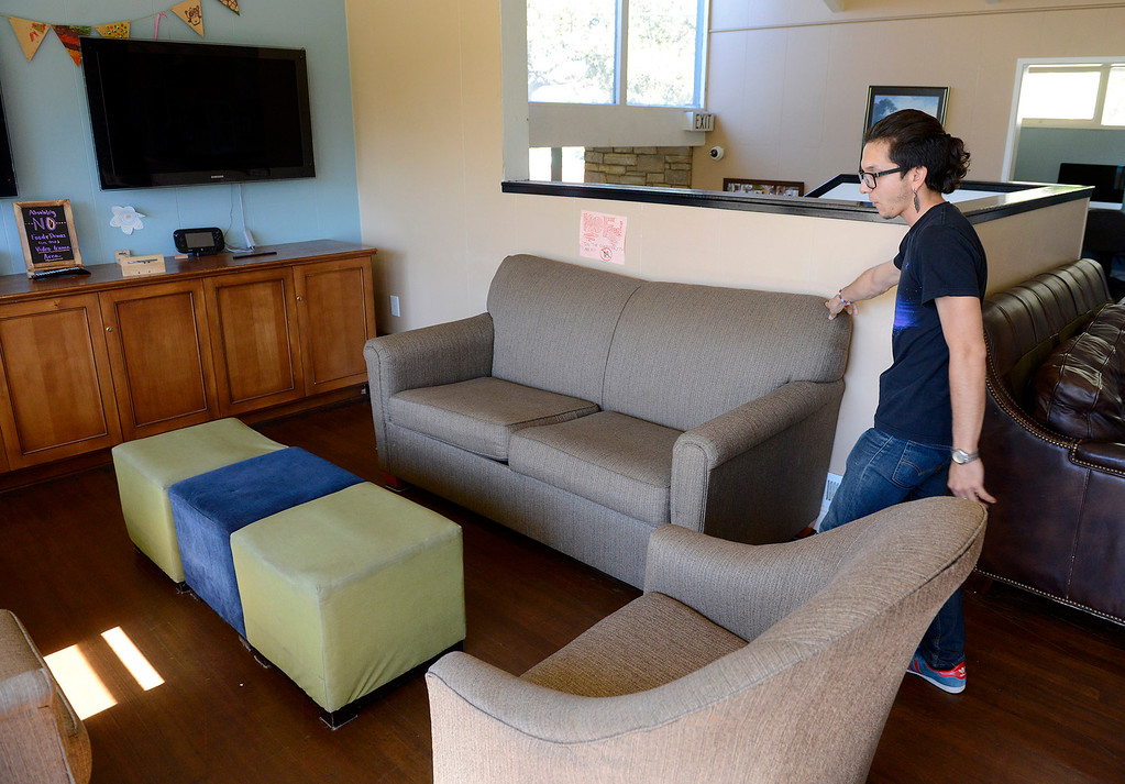 . Thomas Sanchez with the Carmel Youth Center arranges furniture at their facility on Tuesday, Oct. 24, 2017.  The used furniture was received from the Embassy Suites in Seaside.  (Vern Fisher - Monterey Herald)