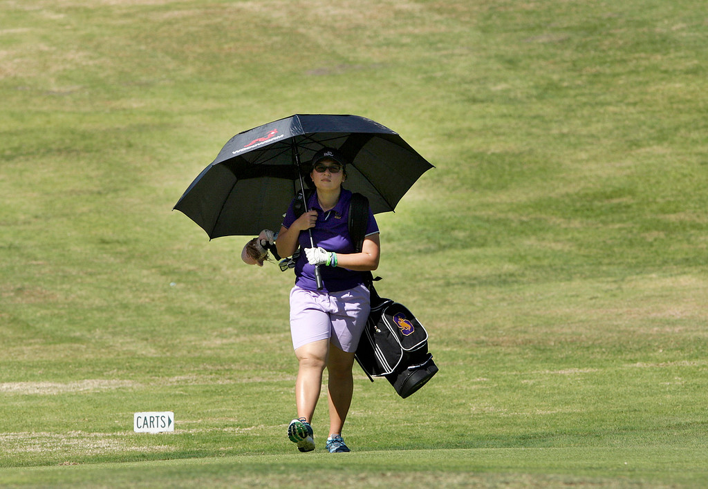 . Salinas High\'s Tara Birgani uses an umbrella for shade in the 100 degree heat during the MBL golf championships at Laguna Seca Golf Ranch in Monterey on Tuesday, Oct. 24, 2017.  (Vern Fisher - Monterey Herald)