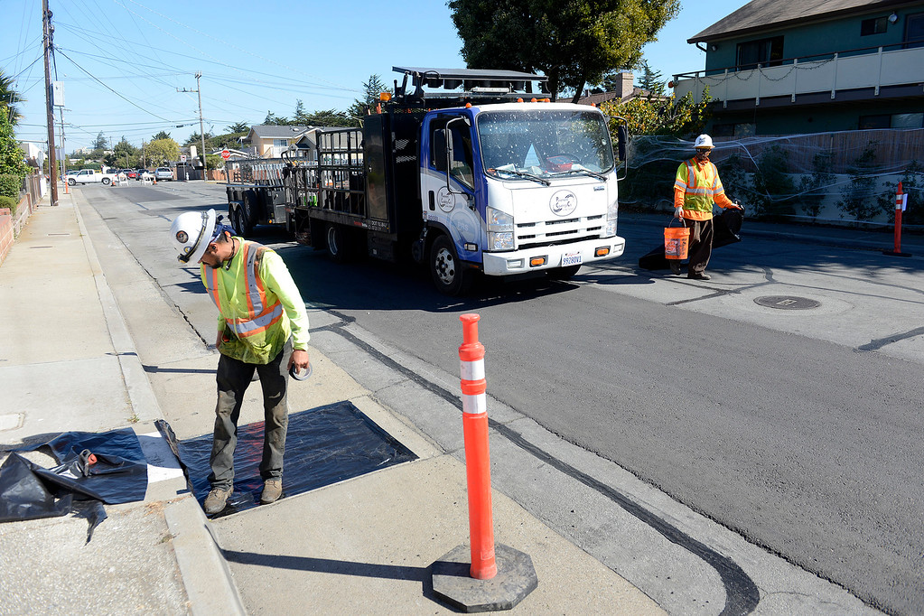 . Jesus Montenez and Ahmad Lloyd prepare for paving work on Encina Ave. in Monterey on Friday, Oct. 27, 2017 as part of Measure P.   (Vern Fisher - Monterey Herald)