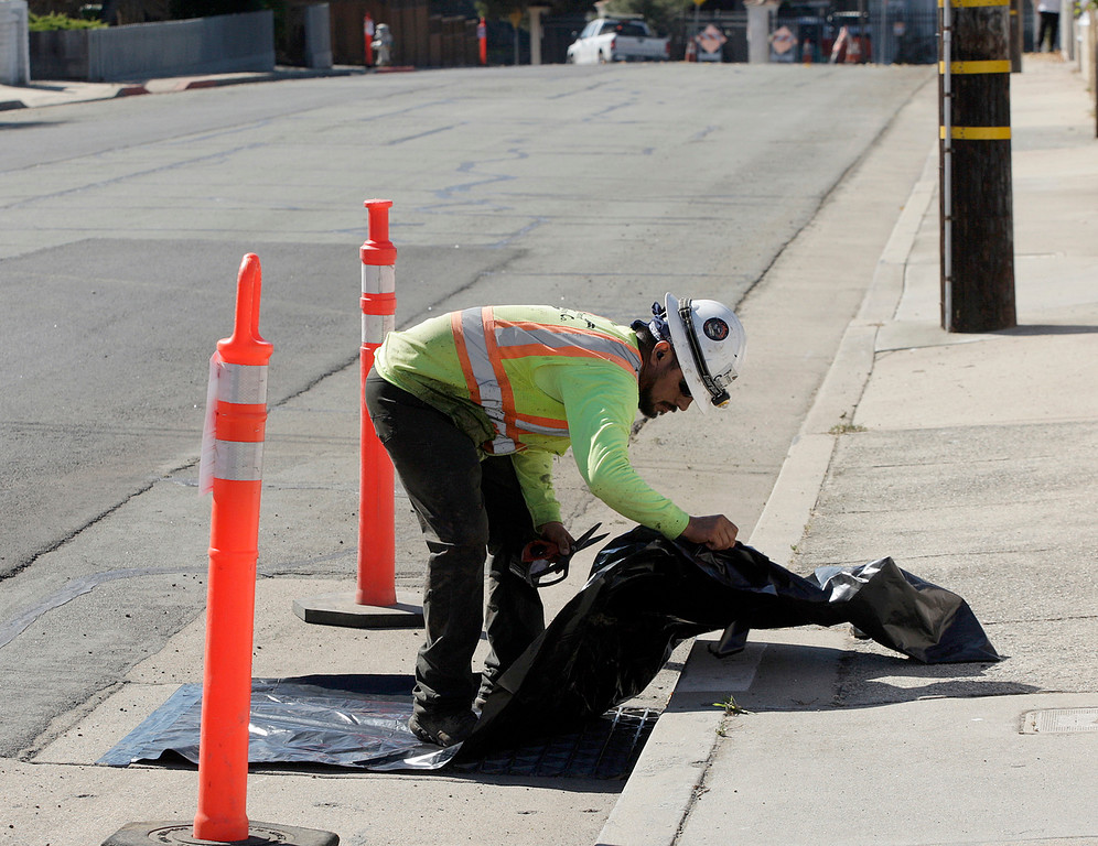 . Jesus Montenez covers a storm drain in prepartion for paving work on Encina Ave. in Monterey on Friday, Oct. 27, 2017 as part of Measure P.   (Vern Fisher - Monterey Herald)