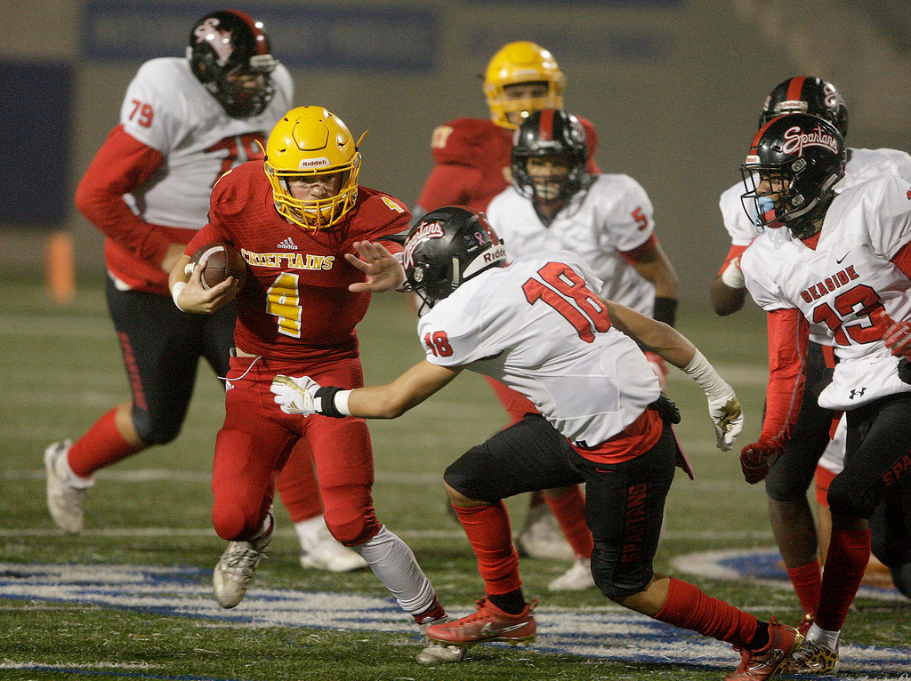 . Palma\'s Peter Powers (4) avoids Seaside\'s Abraham Ramirez (18) as he runs for yards in the first half of their game against Seaside High at Rabobank Stadium in Salinas on Oct. 27, 2017.   (Vern Fisher - Monterey Herald)