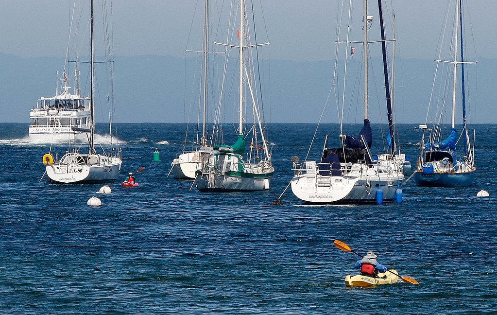 . A kayaker paddles towards moored boats off Monterey Harbor on Friday, September 14, 2018.  (Vern Fisher - Monterey Herald)
