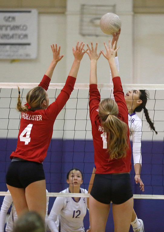 . Salinas\' Taylor Rose spikes the ball against Hollister\'s Lauren Sabbatini and Elizabeth Fleming during girls volleyball at Salinas High School on Tuesday September 26, 2017. (David Royal/Herald Correspondent)