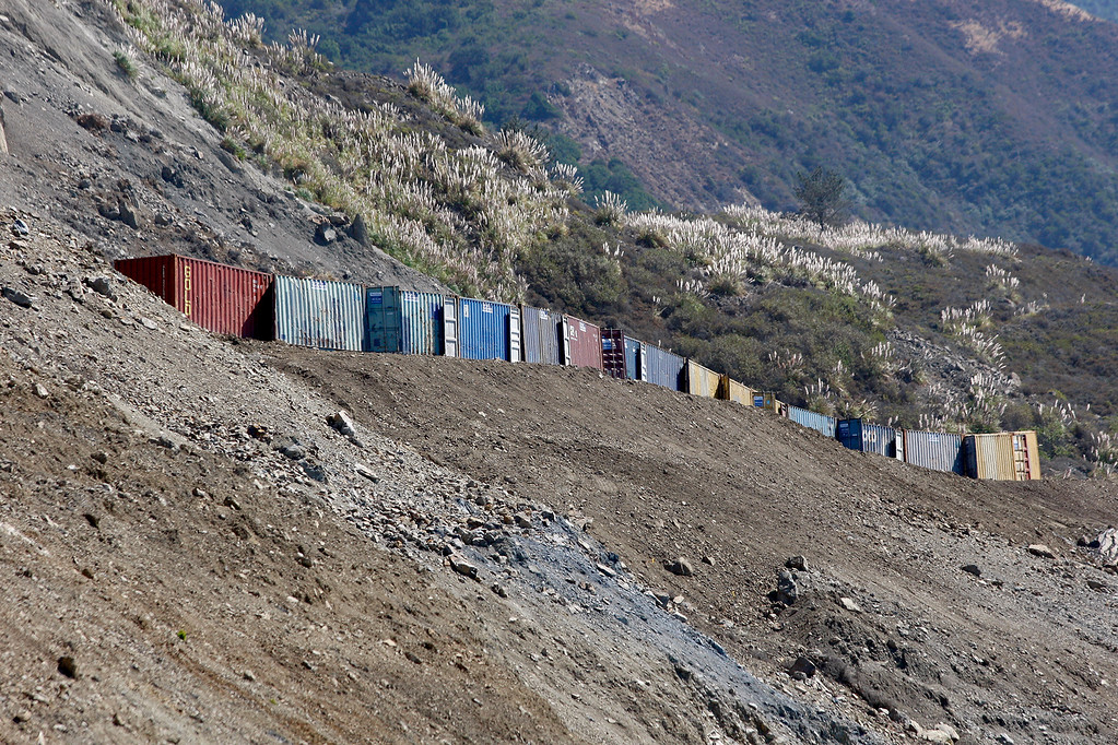 . A wall of cargo boxes was placed half way up the Mud Creek Slide in southern Monterey County on Highway One on Thursday, Sept. 21, 2017 for protection of the workers below.   (Vern Fisher - Monterey Herald)