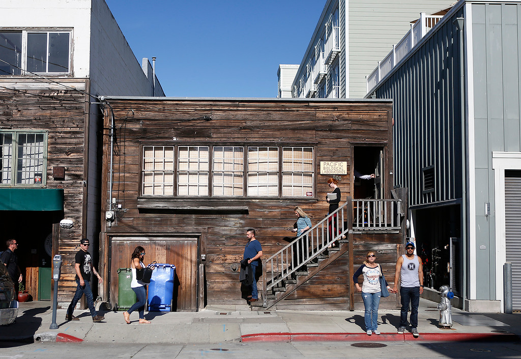 . Monterey aquarium staff members walk down the stairs of Doc Ricketts Lab as other pedestrians pass by on Cannery Row in Monterey on Monday September 25, 2017. Frank Wright, the last living member of Doc Ricketts Lab Club recently passed away. (David Royal/Herald Correspondent)