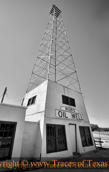 """Title:    Bob's Oil Well is Back ... Sort Of<br /> <br /> Comments: Luther Bedford """"Bob"""" Robertson built a service station on the edge of Matador in 1932 and soon added a wooden derrick to attract truckers. He later rebuilt the station around a steel derrick with lights climbing into the night sky. At the intersection of U.S. 70 and TX 70, Robertson's travelers' oasis was known as the best place to get a hamburger in the Panhandle. He enticed visitors with a zoo of rattlesnakes, bears, monkeys, coyotes, and a buffalo. The enterprise eventually included a grocery store, a garage, and a cafe made of stone and petrified wood.<br /> <br /> Two weeks after Robertson died in 1947, the derrick fell in high winds. His widow restored the tower, but the business closed in the 1950s.   Things deteriorated over the next few decades. Locals have taken to preserving what's left, which stands as one of the earliest examples of American roadside architecture.<br /> <br /> Location: Matador, Texas"""