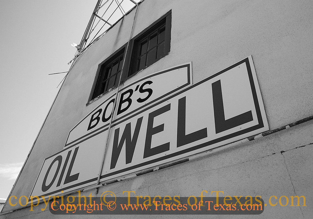 """Title:   Bob Was Mighty Proud of his Oil Well<br /> <br /> Luther Bedford """"Bob"""" Robertson built a service station on the edge of Matador in 1932 and soon added a wooden derrick to attract truckers. He later rebuilt the station around a steel derrick with lights climbing into the night sky. At the intersection of U.S. 70 and TX 70, Robertson's travelers' oasis was known as the best place to get a hamburger in the Panhandle. He enticed visitors with a zoo of rattlesnakes, bears, monkeys, coyotes, and a buffalo. The enterprise eventually included a grocery store, a garage, and a cafe made of stone and petrified wood.<br /> <br /> Two weeks after Robertson died in 1947, the derrick fell in high winds. His widow restored the tower, but the business closed in the 1950s.   Things deteriorated over the next few decades. Locals have taken to preserving what's left, which stands as one of the earliest examples of American roadside architecture.<br /> <br /> Location: Matador, Texas"""
