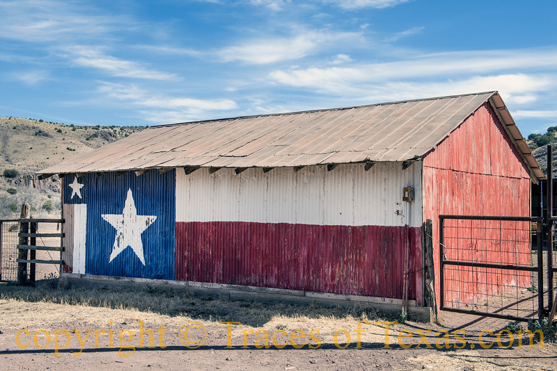Metal side of a barn, decorated with a painting of the Flag of Texas, near Fort Davis in Jeff Davis County, Texas.