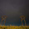 Title:   It was a Dark and Stormy Sight<br /> <br /> Comments: Rainbow above powerlines over field under barbed wire.<br /> <br /> Location: Near Lazbuddie, Texas