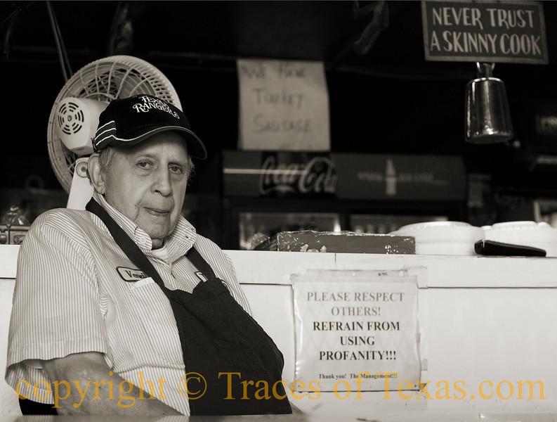 "Title: Barbecue Zen Master<br /> <br /> Comments.  I took this photo of Texas barbecue legend Vencil Mares at his barbecue place, the Taylor Cafe. Mr. Mares is 88 years old and a World War II veteran of the Normandy landing (D-day), the Battle of the Bulge, and the Battle of Bastogne. He served as a medic, then came back to Texas and has been cooking barbecue for the last 65 years. I asked him what the secret to his long life is and he smiled and said ""barbecue is health food."" He's a Texas treasure, rightly revered, and it was good to see him holding court. <br /> <br /> Location: Taylor"