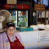 "Title: Barbecue Zen Master<br /> <br /> Comments. I took this photo of Texas barbecue legend Vencil Mares at his barbecue place, the Taylor Cafe. Mr. Mares is 88 years old and a World War II veteran of the Normandy landing (D-day), the Battle of the Bulge, and the Battle of Bastogne. He served as a medic, then came back to Texas and has been cooking barbecue for the last 65 years. I asked him what the secret to his long life is and he smiled and said ""barbecue is health food."" He's a Texas treasure, rightly revered, and it was good to see him holding court.<br /> <br /> Location: Taylor"