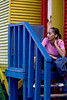 A woman watches her children play (out of frame). Taken at the colorful beach houses of Muizenberg, South Africa, Africa.