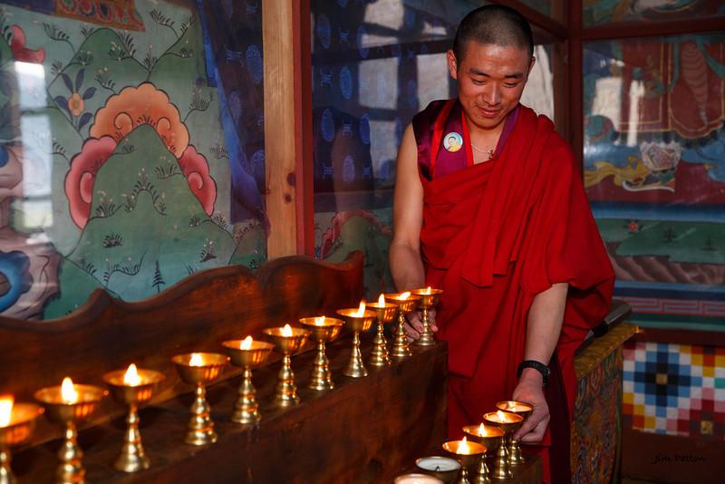 Monk lighting candles at Paro Dzong