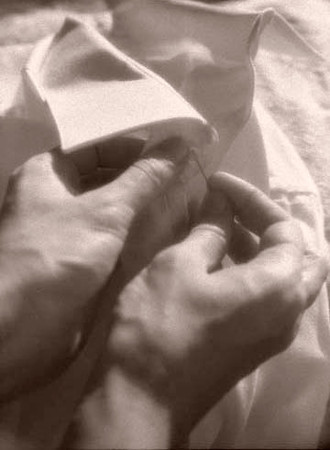 Woman's hands sewing button on man's shirt.