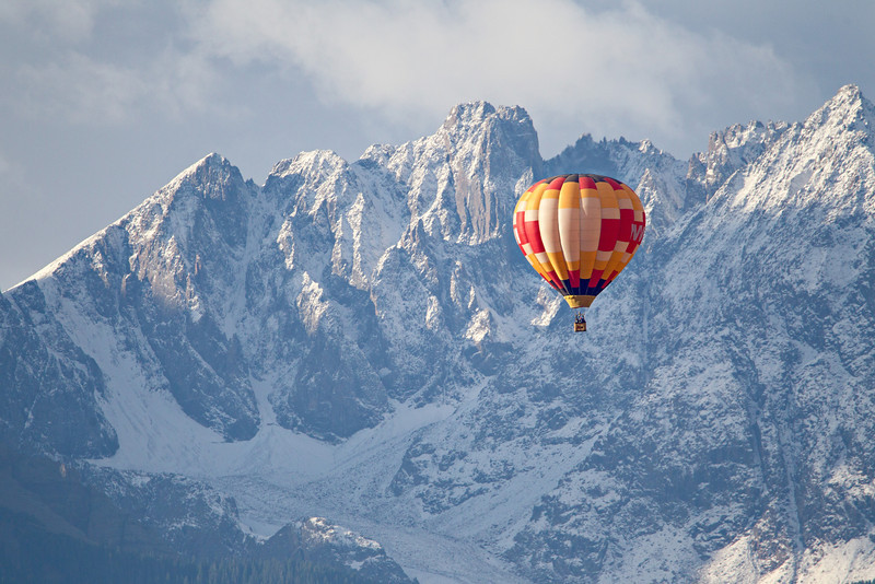 A hot air balloon floats in the sky, with the San Juan Mountains in the background. Taken in Ouray County, Colorado, USA.