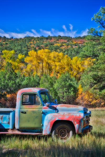 An old truck with its paint gradually being replaced by rust. Taken on a county road near Ridgway, Colorado, USA.
