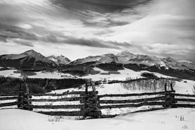 """The Wilson Massif in Winter""  A rustic fence with the San Miguel mountains of the San Juan range in the background. The mountains include Mt. Wilson, Wilson Peak, and El Diente, all of which are fourteeners (mountains over 14,000 feet in altitude). Taken near Telluride, Colorado, USA."