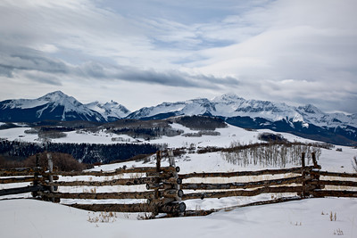 """The Wilson Massif in Winter (Color Version)""  A rustic fence with the San Miguel mountains of the San Juan range in the background. The mountains include Mt. Wilson, Wilson Peak, and El Diente, all of which are fourteeners (mountains over 14,000 feet in altitude). Taken near Telluride, Colorado, USA."