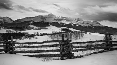 A rustic fence with the San Miguel mountains of the San Juan range in the background. The mountains include Mt. Wilson, Wilson Peak, and El Diente, all of which are fourteeners (mountains over 14,000 feet in altitude). Taken near Telluride, Colorado, USA.