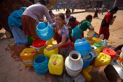 women with coloured plastic drums and copper pitchers at the well
