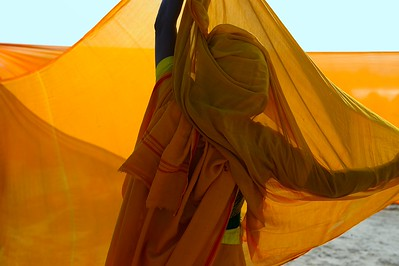 after taking holi dip in the river, women hang their sarees in the wind