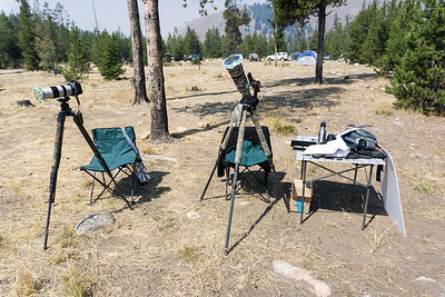 My setup for shooting the eclipse. I chose to sit in the chairs for most of the shots, although a few were taken handheld, too. The portable table holds all of the assorted paraphernalia I wanted to try out, plus notes for settings, an iPad for timing the shots every 10 minutes, an iPhone to run more apps, drinks, snacks, my Sony camera for people and setup shots, a colander, cheese grater, slotted spoon, gaffer tape (just in case!) and white foamcore for projecting images. Taken in the Sawtooth National Recreation Area, Idaho, USA.