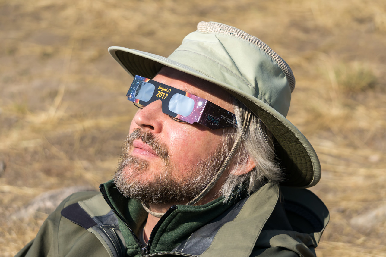 James Hager takes in the August 21, 2017 total eclipse of the sun using his eclipse glasses. I had ordered a set of eclipse glasses online; they never arrived, I assume due to the supply running out. Then James ordered a set on eBay; they never arrived in time. Thankfully, the public library in Stanley, Idaho was giving them away for free. So we were finally prepared! Taken in the Sawtooth National Recreation Area, Idaho, USA.