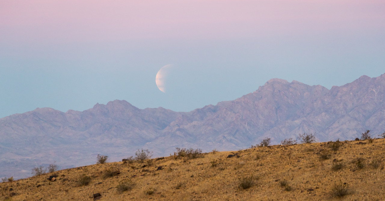 The partially eclipsed moon just as it is about to set behind the mountains during the total lunar eclipse of January 31, 2018. There were some streaky clouds that lent an unusual appearance to the moon. Taken at Standard Wash BLM area, south of Lake Havasu City, Arizona, USA.