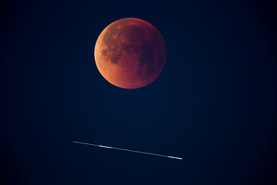 """A Plane and the Eclipsed Moon"""