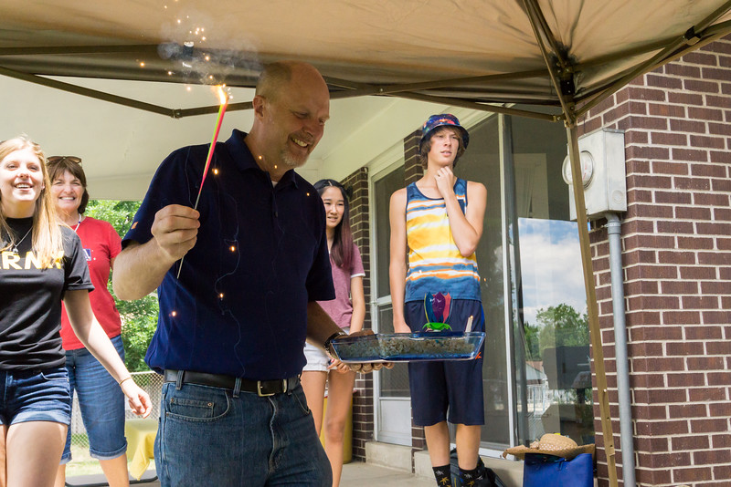 Ron Forseth carries out the cake and a sparkler to celebrate the twins' birthdays.