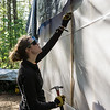 Erica France nails the lath in place. It holds up the construction plastic. Don't swallow the next nail, E!