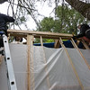 Three people on ladders! Steve Hansen and Erica France work on the outside, while James Hager works from the inside of the tiny house. They were all installing a rim joist near the top of the structure.